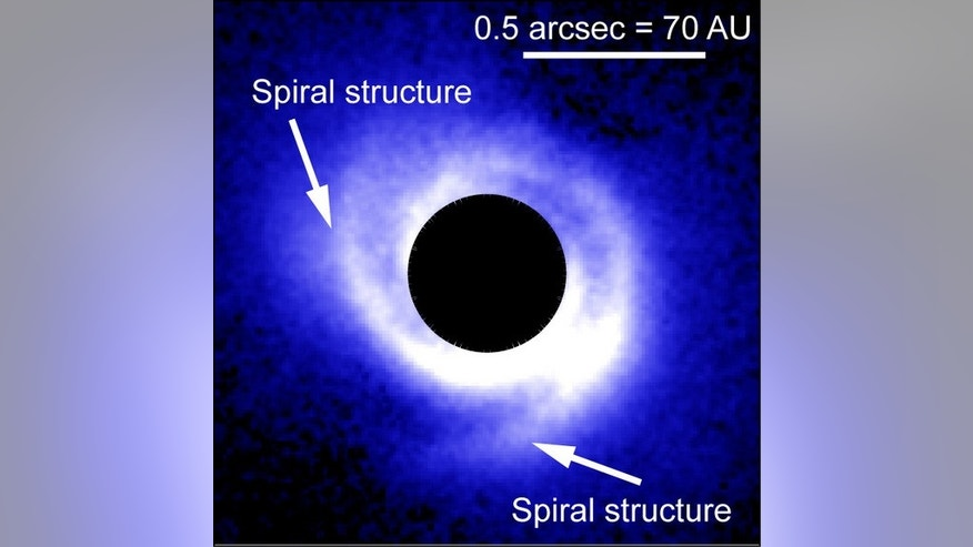 An image of the disk around SAO 206462 captured with HiCIAO. A coronagraph blocks the direct light of the central star, which appears as the black, circular area in the image. Arrows show the two arms of the spiral structure around the star.