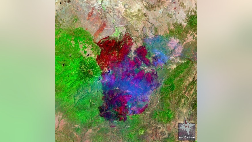 A Landsat 5 image of the Wallow Fire, the largest wildfire in Arizona's history. In this image, acquired on June 15, 2011 the burn scar is red, ongoing fires are very bright red, smoke is blue, water is black and dark blue and bare ground is ta