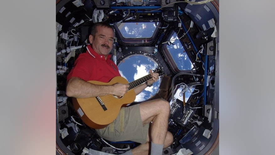 Canadian astronaut Chris Hadfield strums a guitar while playing Christmas carols and gazing at Earth from the International Space Station in December 2012.