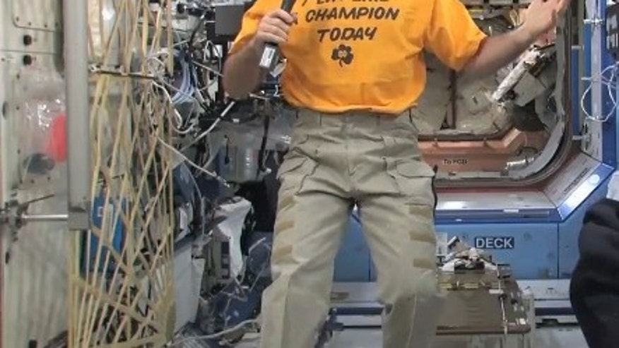 "NASA astronaut Kevin Ford smiles while wearing his Notre Dame ""Play Like a Champion Today"" shirt on Dec. 26 to support the college's BCS Championship Game against Alabama on Jan. 7, 2013. Ford is the commander of Expedition 34 aboard the Intern"
