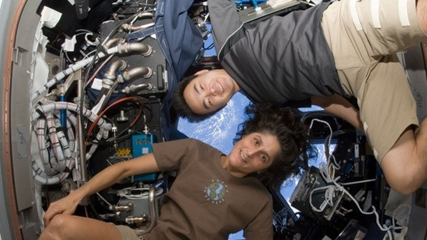 NASA astronaut Sunita Williams, Expedition 33 commander; and Japan Aerospace Exploration Agency astronaut Aki Hoshide, flight engineer, pose for a photo in the Cupola of the International Space Station. This image was taken Sept. 23, 2012.