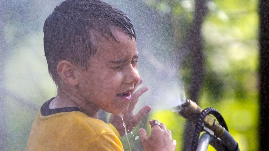 July 6, 2012: Six-year-old Alexander Merrill of Sioux Falls, S.D., cools off in a cloud of mist at the Henry Doorly Zoo in Omaha, Neb., as temperatures reached triple digits.