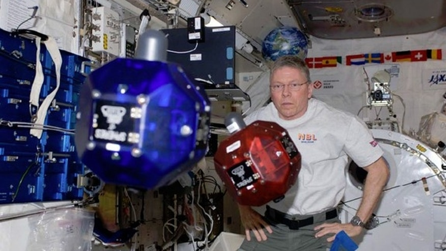 NASA Astronaut Mike Fossum operates small, autonomous satellites aboard the International Space Station in November 2011. Every year, high school students compete to submit computer code to run in the satellites, called SPHERES.