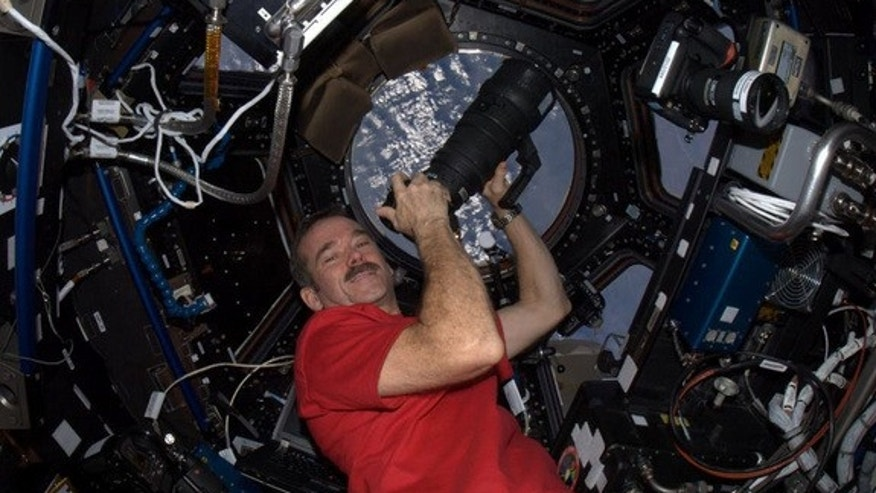 Canadian astronaut Chris Hadfield poses with a camera in the Cupola of the International Space Station, which serves as the observation deck, during the Expedition 34 mission in January 2013.