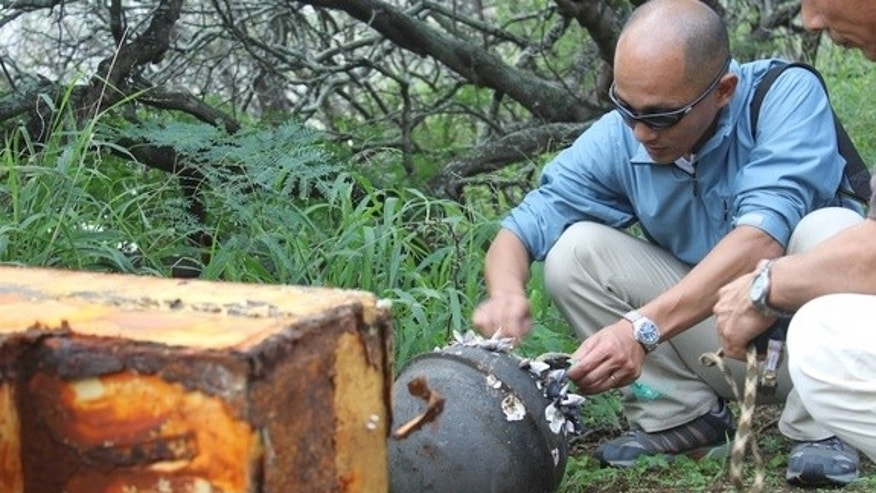 Researchers examine a buoy and refrigerator traced to the 2011 Japan tsunami. Debris like this is not normally seen in Hawaii, but the tsunami has sent a number of unusual items across the Pacific.
