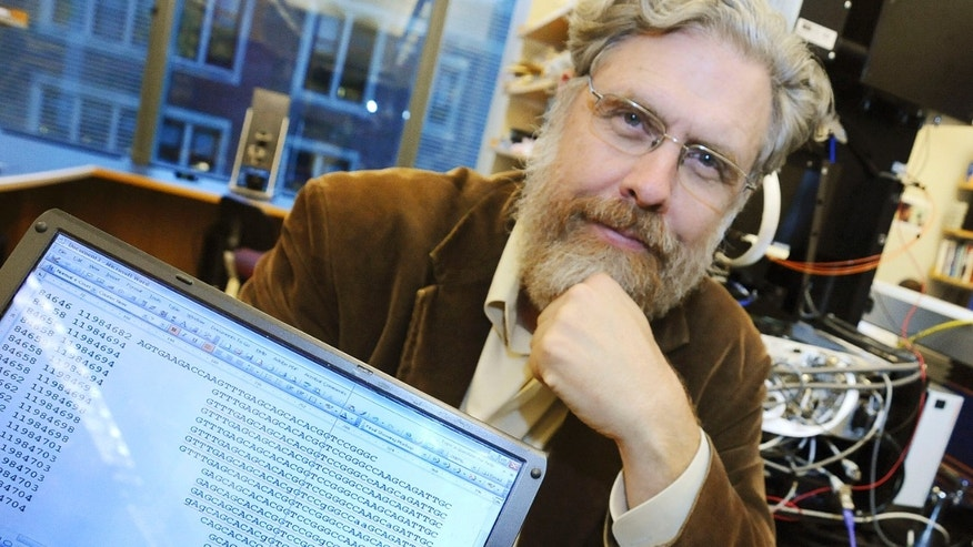 In this Oct. 20, 2008 file photo, Harvard Medical School genetics professor George Church poses for a photo with DNA sequence data for Dr. John Halamka, chief information officer, following a news conference in Boston.