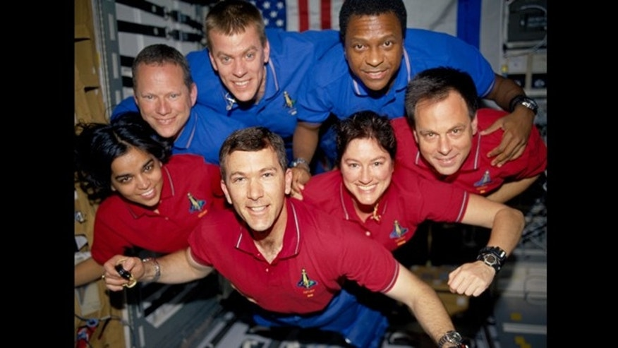 During the STS-107 mission, the crew appears to fly toward the camera in a group photo aboard the Space Shuttle Columbia. On the bottom row (L to R) are astronauts Kalpana Chawla, mission specialist; Rick D. Husband, mission commander; Laurel B. Clark, mission specialist; and Ilan Ramon, payload specialist. In the top row (L to R) are astronauts David M. Brown, mission specialist; William C. McCool, pilot; and Michael P. Anderson, payload commander. On February 1, 2003, during re-entry, the Space Shuttle Columbia disintegrated over northern Texas with all seven crewmembers aboard. This picture survived on a roll of unprocessed film recovered by searchers from the debris.