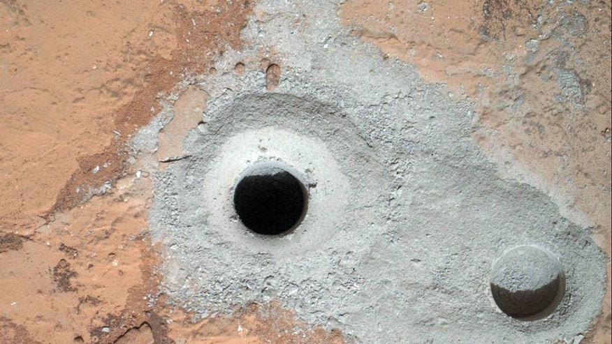 Feb. 9, 2013: This image released by NASA shows a fresh drill hole, center, made by the Curiosity rover on Friday, Feb. 8, 2013 next to an earlier test hole.
