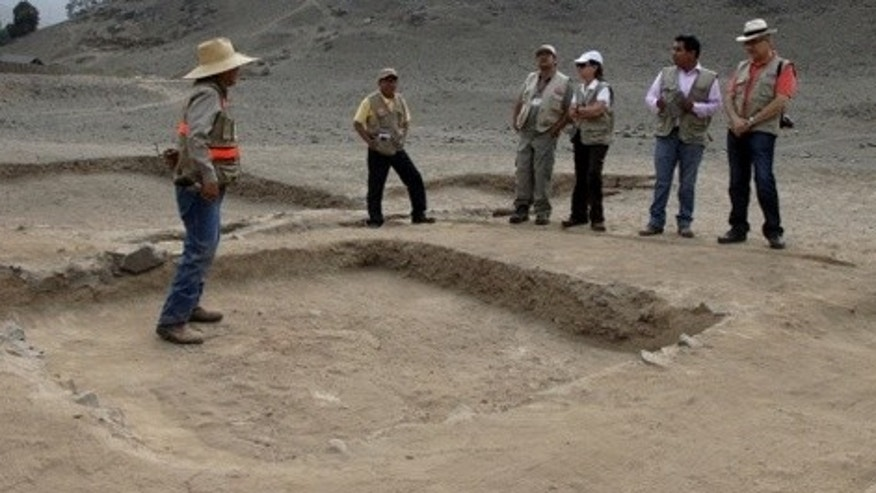 Excavators stand near a newly discovered temple at the archeological site El Paraíso in Peru.