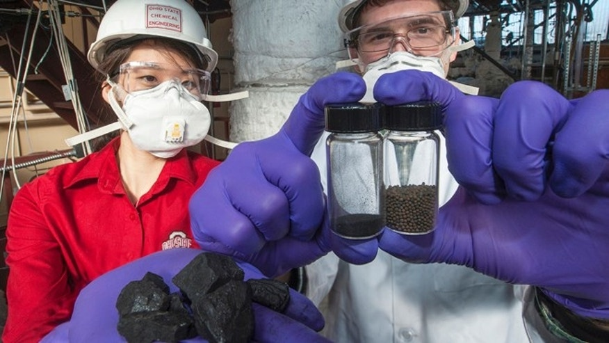 At a research-scale combustion unit at Ohio State University, engineers are testing a clean coal technology that harnesses the energy of coal chemically, without burning it. Here, doctoral student Elena Chung (left) and master&#39&#x3b;s student Samuel Ayham (right) display chunks of coal along with pulverized coal (bottle, center) and the iron oxide beads (bottle, right) that enable the chemical reaction.
