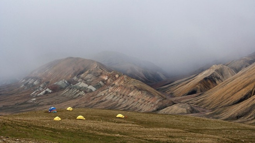 View of Camp 2 at the Fyles Leaf Bed Site on Ellesmere Island, near Strathcona Fiord. Across the valley lay exposed tilted Devonian-era beds, partially obscured by low-lying cloud.