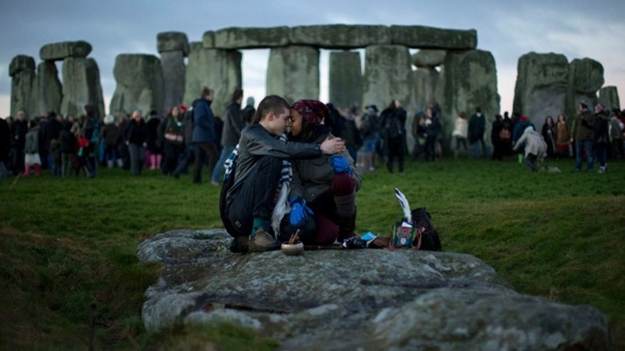 Dec. 21, 2012: People embrace by the ancient stone circle of Stonehenge, in southern England, as access to the site is given to druids, New Age followers and members of the public on the annual Winter Solstice. British researchers have proposed a new theory for the origins of Stonehenge: It may have started as a giant burial ground for elite families around 3,000 B.C. (AP)