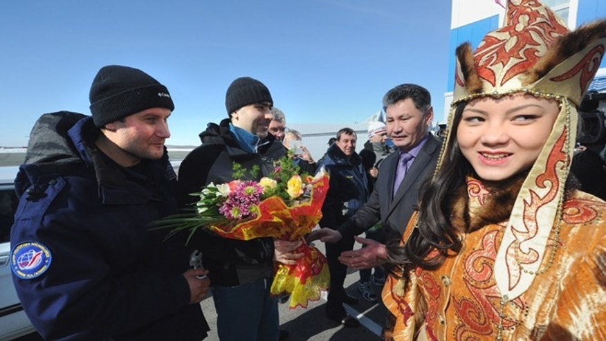 March 16, 2013: Russian cosmonauts Oleg Novitsky, left, and Yevgeny Tarelkin, second left, are greeted with flowers upon arrival at an airport in Kostanai, Kazakhstan, after they return to the earth with NASA's astronaut Kevin Ford, not in the photo, in a Soyuz space capsule.