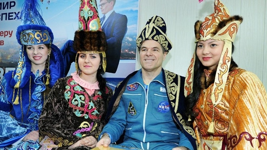 March 16, 2013: NASA's astronaut Kevin Ford, wearing a Kazakh traditional costume, poses for a photo with Kazakh women in national costume, at an airport in Kostanai, Kazakhstan, after his return to the earth with Russian cosmonauts Oleg Novitsky and Yevgeny Tarelkin.