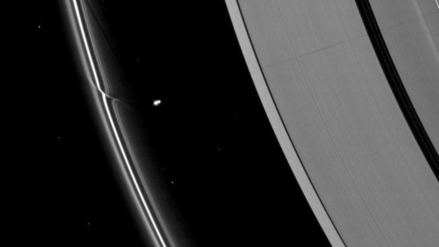 The effects of the small moon Prometheus loom large on two of Saturn's rings in this image taken a short time before Saturn's August 2009 equinox.  A long, thin shadow cast by the moon stretches across the A ring on the right. The gravity of po