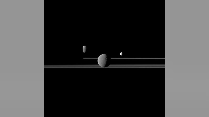 The Cassini spacecraft observes three of Saturn's moons set against the darkened night side of the planet. Saturn is present on the left this image but is too dark to see. Rhea (1,528 kilometers, or 949 miles across) is closest to Cassini here