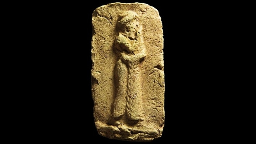 April 1, 2013: A clay plaque, which shows a worshipper approaching a sacred place. He is wearing a long robe with fringe down the front opening, found during an excavation Tell Khaiber, Iraq.