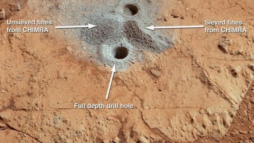 The first drill holes on Mars by NASA's Curiosity rover are seen in this image taken by the rover on March 29, 2013 at the John Klein rock in the Yellowknife Bay area of Mars' Gale Crater.