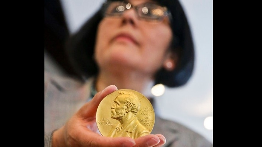 April 10, 2013: Sandra Palomino, director of historical manuscripts at Heritage Auctions, holds the1962 Nobel Prize for Physiology or Medicine awarded to Dr. Francis Harry Compton Crick. On Thursday, the molecular biologist's medal and accompanying diploma will be sold by Heritage Auctions, which estimates it could fetch at least $500,000.
