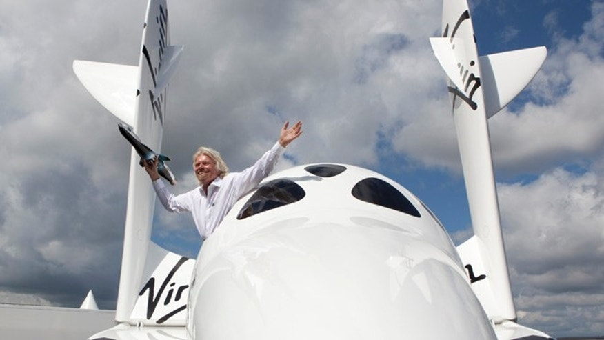 Sir Richard Branson in SpaceShipTwo holding a model of LauncherOne.