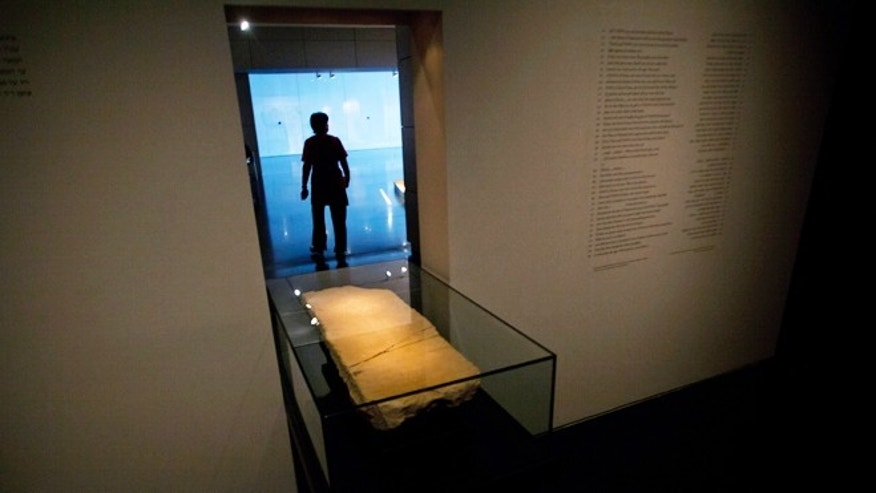 April 30, 2013: A museum worker walks next to the 'Gabriel Stone' as it is displayed at an exhibition at the Israel Museum in Jerusalem.