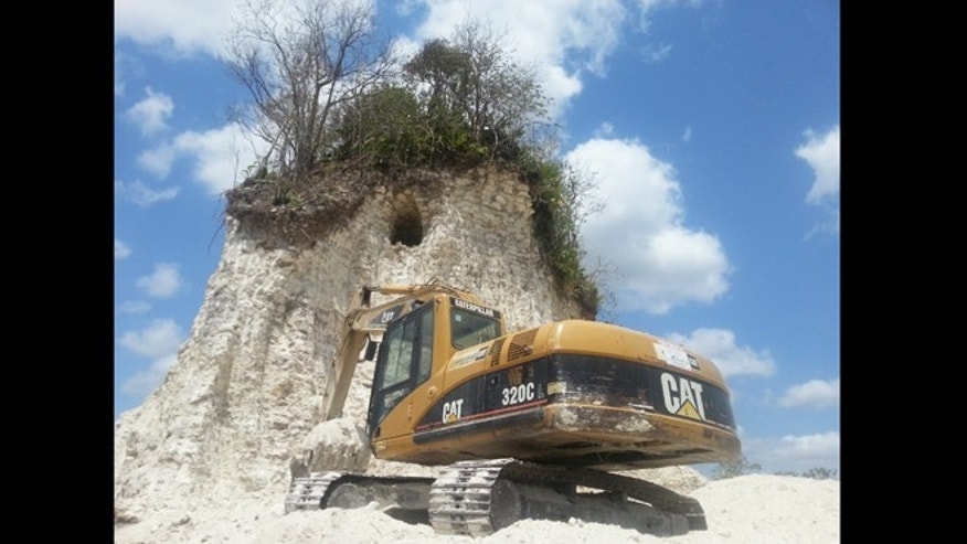 "Heavy construction equipment sits dormant at the remains of a partially destroyed Mayan temple, part of the 3,200 year old site known as Noh Mul or ""Big Hill."""