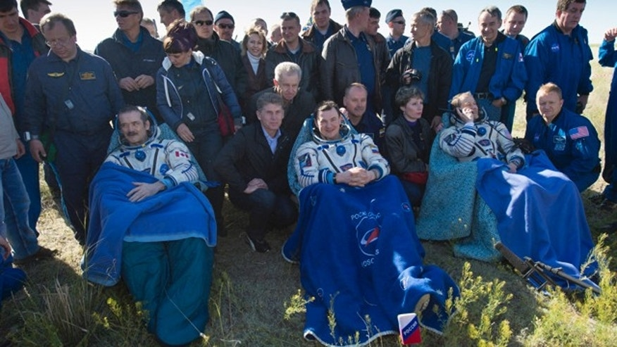 May 14, 2013: Commander Chris Hadfield of the Canadian Space Agency (CSA), left, Russian Flight Engineer Roman Romanenko of the Russian Federal Space Agency (Roscosmos), center, and NASA Flight Engineer Tom Marshburn sit in chairs outside the Soyuz Capsule just minutes after they landed in a remote area outside the town of Dzhezkazgan, Kazakhstan.