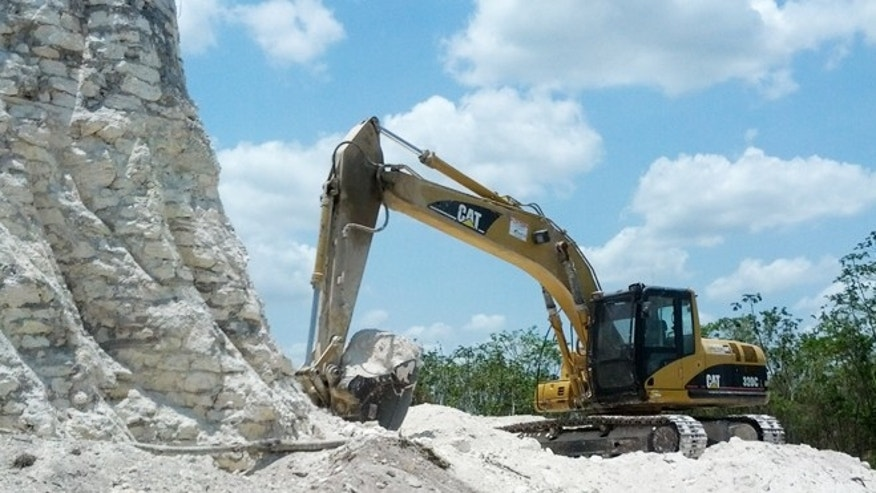 May 13, 2013: A backhoe claws away at the sloping sides of the Nohmul complex, one of Belize's largest Mayan pyramids on May 10, 2013 in northern Belize.