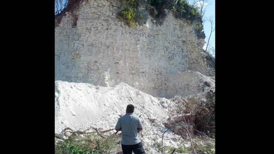 May 13, 2013: A man looks up at the damaged sloping sides of the Nohmul complex, one of Belize's largest Mayan pyramids in northern Belize. A construction company has essentially destroyed the pyramid with backhoes and bulldozers to extract crushed rock for a road-building project.