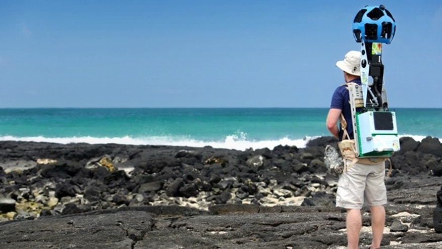 In this May 2013 photo provided by Google, Daniel Orellana of the Charles Darwin Foundation collects seashore imagery with the Street View Trekker at the Los Humedales wetland area on Isabela Island in the Galapagos. Few have laid eyes on many of the volcanic islands of the Galapagos archipelago that remain closed to tourists.