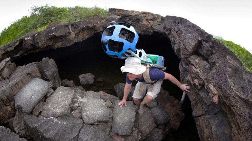 In this May 2013 photo provided by Google, Daniel Orellana of the Charles Darwin Foundation climbs out of an Isabela island where he was collecting imagery on the Galapagos.