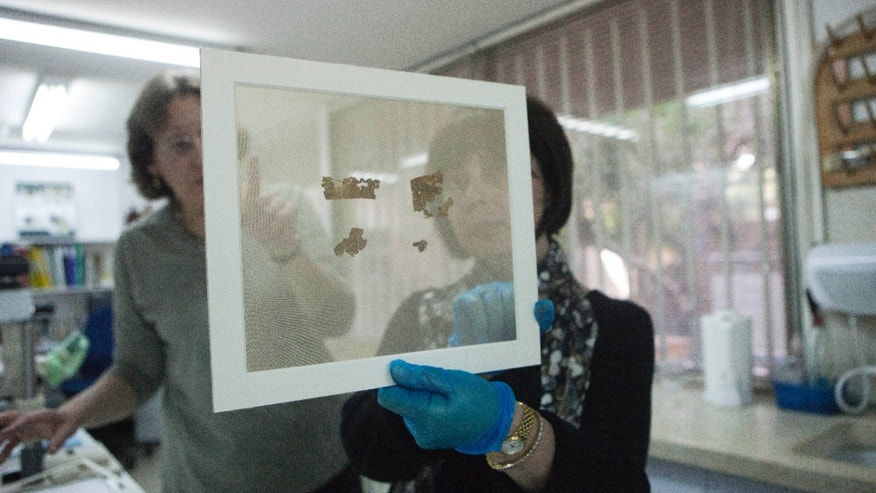 May 10, 2013: Lena Libman, right, head of the Israel Antiquities Authority's Dead Sea Scrolls Conservation Lab holds fragments of the Dead Sea Scrolls in Jerusalem.