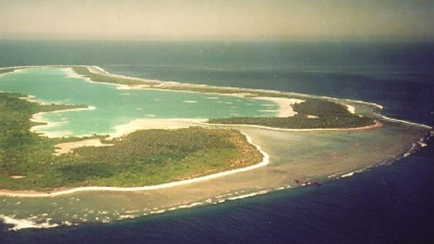 Nikumaroro (formerly Gardner Island) looking southeastward at low tide. Note the broad, dry reef-flat which surrounds the atoll. The rusting remains of the steamer S.S. Norwich City can be seen on the reef edge at right center. This photo was taken in 1978.