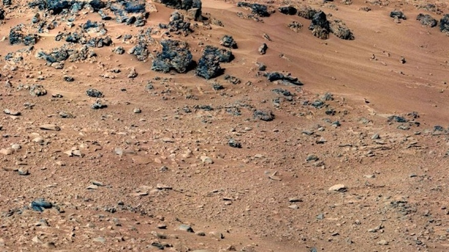 "The patch of windblown sand and dust downhill from a cluster of dark rocks labeled the ""Rocknest"" site, where eagle-eyed believers think they've uncovered a ""space rat."""