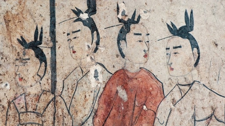 "A close-up of four of the female attendants under a parasol. Notice the detail of their ""flying bird"" hairstyles."