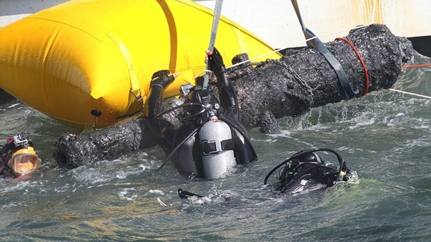 June 20, 2013: Divers emerge with one of two cannons raised from the wreck of the Queen Anne's Revenge off the coast of Carteret County, N.C.