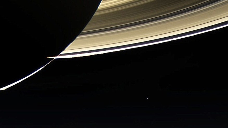 A photo by the Cassini spacecraft shows the rings of Saturn, with Earth a faint blue dot in the distance.