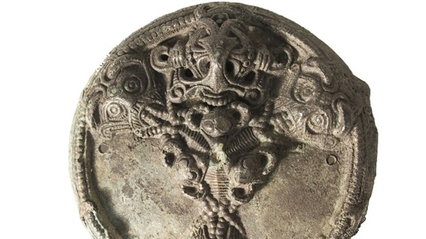 A copper alloy piece of jewelry found at a Viking-age site in Denmark shows an animal figure with a beadlike chain around its neck.