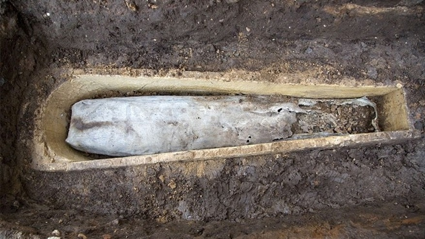 The lead coffin can be seen inside of the stone coffin found at the Greyfriars dig site. Damage to the right side of the lead coffin reveals the feet of the unknown deceased inside.