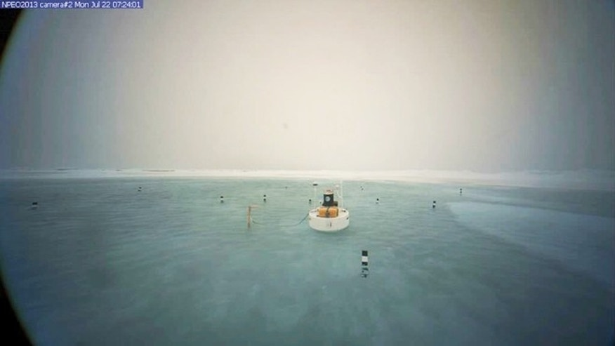 July 22, 2013: A picture of a buoy anchored near a remote webcam at the North Pole shows a meltwater lake surrounding the camera.