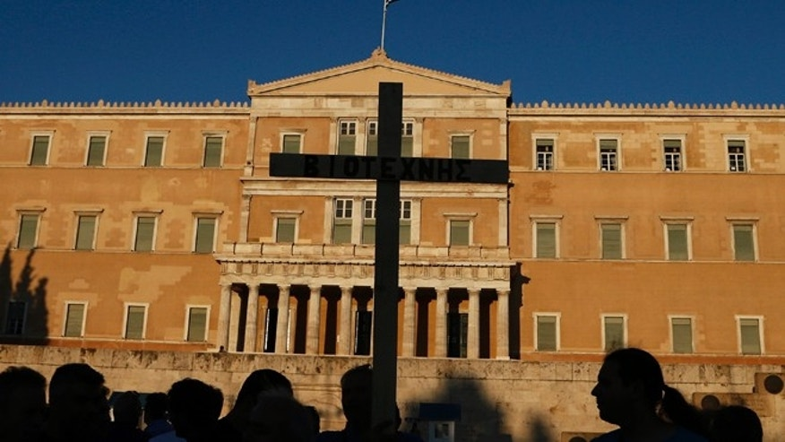 July 23, 2013: Protesters holding a cross are silhouetted in front of the Parliament during a protest rally in Athens.