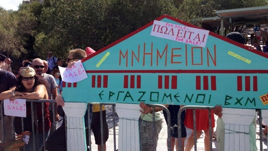 Aug. 2, 2013: Greek state archaeologists hold a Styrofoam model of a temple, with 'For Sale' signs stuck on it, during a protest in front of the ancient Acropolis hill in Athens.