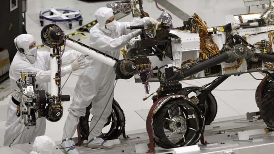 FILE - This Sept. 16, 2010 file photo shows engineers working on the Mars rover Curiosity at NASA's Jet Propulsion Laboratory in Pasadena, Calif. Curiosity celebrated its first year on Mars and is driving toward a mountain in a journey that will take months.(AP Photo)
