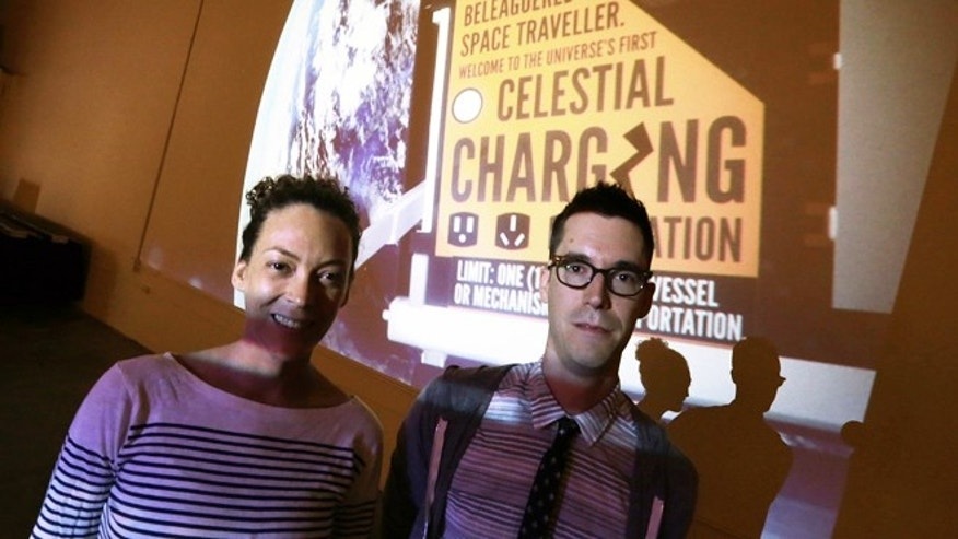 July 31, 2013: Jon Gibson and Amanda White pose with a projected image of their artwork that will be launched into space, at their studio in the Echo Park district of Los Angeles.