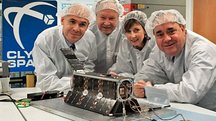 Officials in Glasgow, Scotland, pose in this recent photo with a satellite that will carry artwork created by Los Angeles artists into space. Posing from left are Craig Clark of Clyde Space, Serkey Krutikov, consul general of the Russian Federation in Edinburgh, Lena Wilson, Scottish Enterprise chief executive, and Scotlands First Minster Alex Salmond.