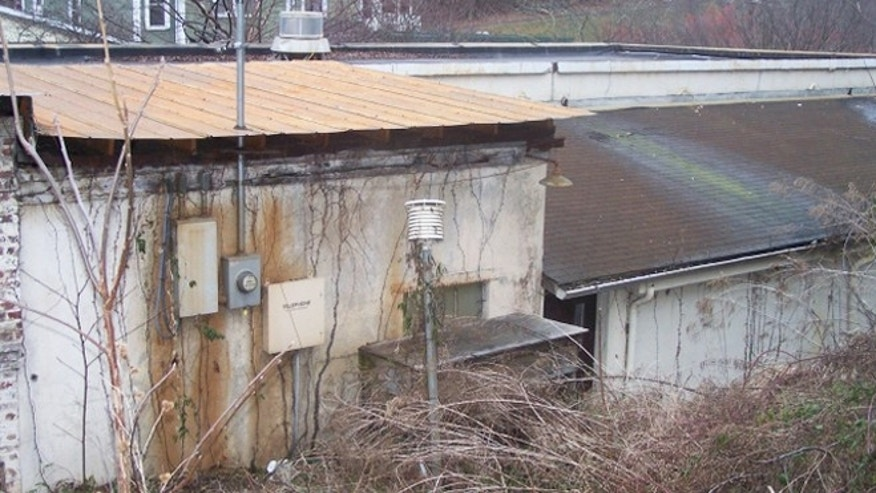 A weather station in Hot Springs, Va., sits next to the wall of a steam power plant and is overgrown with weeds, yet NOAA still operates it -- one of many flawed sites, critics complain.