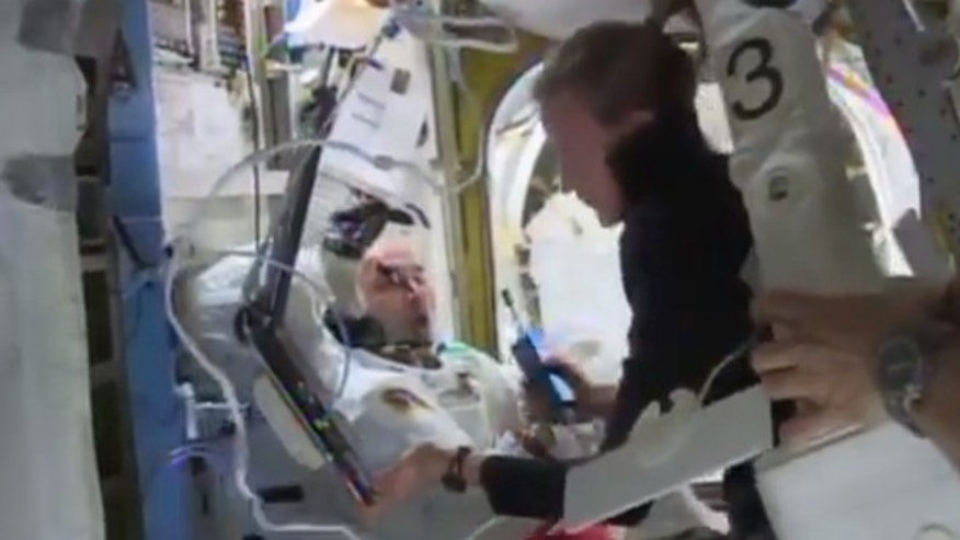 Astronaut Karen Nyberg assists astronaut Luca Parmitano to remove his space suit aboard the International Space Station after the aborted spacewalk on Tuesday, July 16, 2013.
