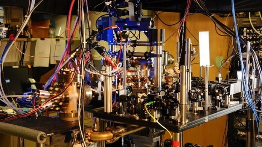 Scientists have designed a new atomic clock, using laser light and ytterbium atoms, that is ten times more stable than previously reported clocks. Ytterbium atoms are generated in an oven (large metal cylinder on the left) and sent to a vacuum