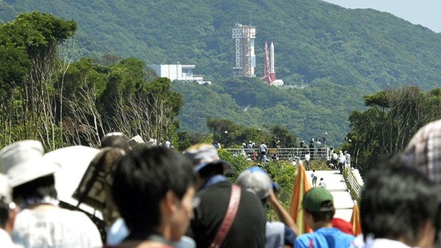 Aug. 27, 2013: Spectators gather to watch an Epsilon rocket, seen in the background, before its launch at the Uchinoura Space Center in Kimotsuki town, Kagoshima, western Japan.