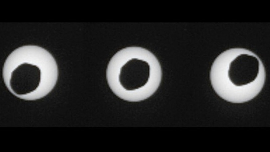 This set of three images taken three seconds apart by NASA's Curiosity rover shows the larger of Mars' two moons, Phobos, passing in front of the sun on Aug. 17, 2013.